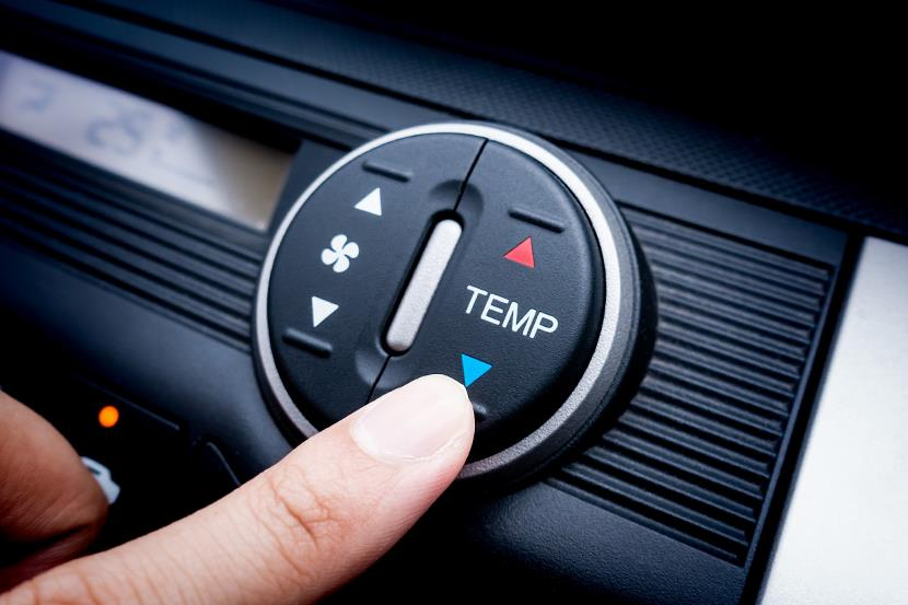 clouseup of persons finger adjusting temperature control on car console