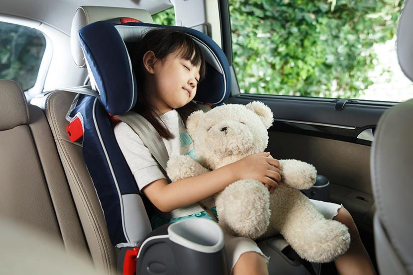 little girl sleeping in car seat while holding a teddy bear