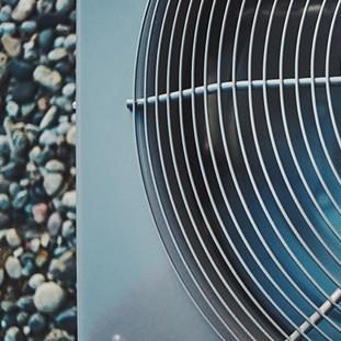 closeup of air conditioner unit with fan running