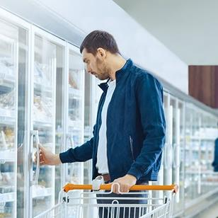 man pushing orange and white shopping cart looking in freezer at grocery store