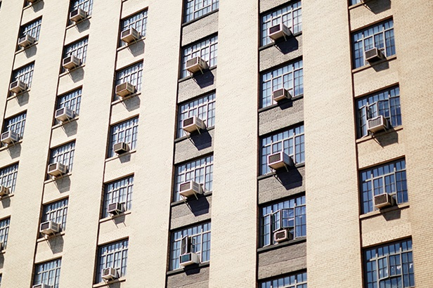 tan apartment building with air conditioning units coming out of most windows