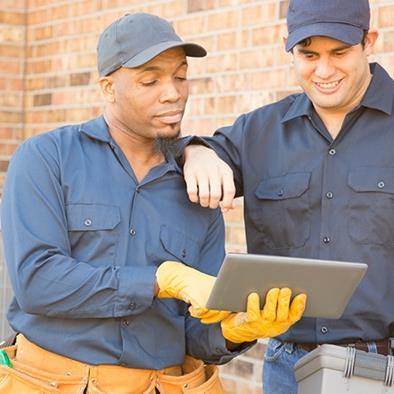 two men in blue standing in front of hvac units and looking at a tablet